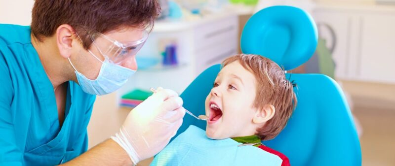 dentist with toddler in exam room