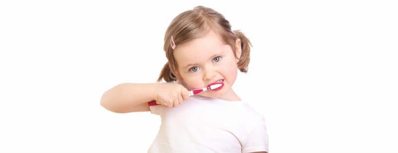 young toddler brushing her teeth