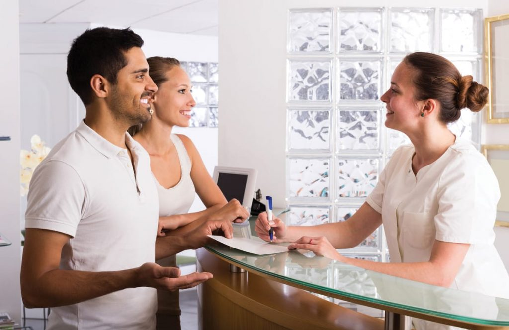 couple at front desk of Calgary dental office